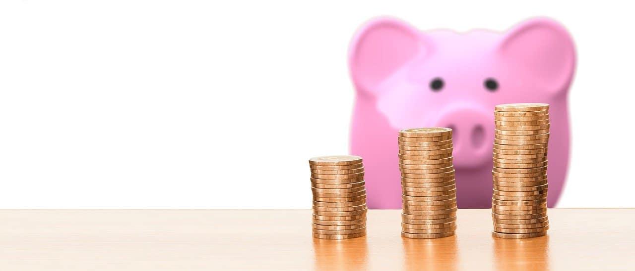 מטבעות וקופת חיסכון של חזיר בצבע ורוד
